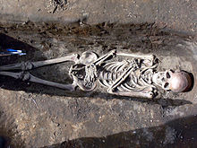 Colour photograph of a human skeleton in an excavated Icelandic grave.
