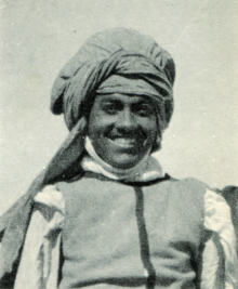 A portrait photograph of Ehnni, a dark-skinned man wearing a turban