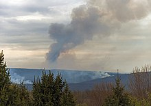 A distant ridge, seen as spring appears to be emerging, with two areas from which white smoke is rising. In the center a large plume of smoke, dark against a cloudy late afternoon sky through which some sunlight is penetrating, rises and bends to the right. In front are some evergreens.