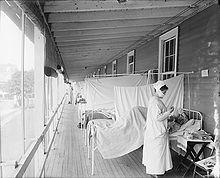 mehrere Krankenbetten von Erkrankten an der Spanischen Grippe, welche nebeneinander auf einem überdachten Balkon stehen, getrennt durch weiße Laken; eine Krankenschwester mit Mundschutz versorgt einen Patienten