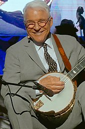 A man wearing a suit and playing a banjo.
