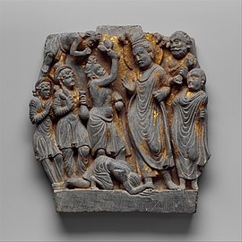 In this panel Sumedha appears three times: first, standing before the Buddha Dipankara offering flowers; second, prostrating before the Buddha spreading his matted locks over mud; and third, flying in the upper left of the panel in a gesture of veneration.