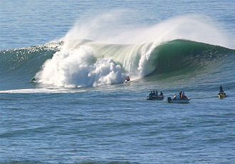 Surf culture - Surfers and spectators in boats at Mavericks, a world-renowned big wave break about 800 meters off the coast of Half Moon Bay, California