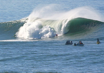 A large wave breaking Surfers at Mavericks.jpg