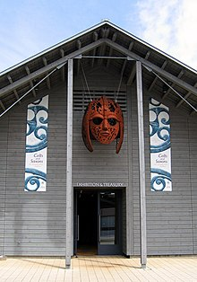 Colour photograph of the exhibition and treasury hall at the Sutton Hoo visitor centre, outside of which hangs the sculpture Sutton Hoo Helmet by Rick Kirby
