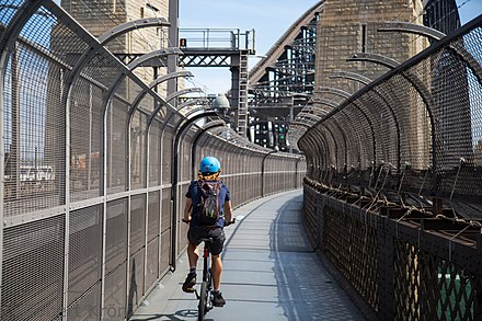 A cyclist using the pedestrian footway. Side fences were added to prevent people from committing suicide by jumping from the bridge. Sydney Harbour Bridge cyclist.jpg