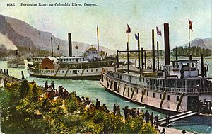 Charles R. Spencer - This photograph is from an old colorized postcard.  The view is towards the west, and shows T.J. Potter pulling away from a landing, probably just before entering the Cascade Locks.  Another steamer, a sternwheeler, is in the foreground, this is possibly the Charles Spencer.  Coming up to the landing from the west another steamer can be seen, which from the vessel's apparent configuration and the white collar on her funnel, appears to be the ''Bailey Gatzert''.  The large crowds on all the steamers are readily visible; this is an excellent depiction of the high point of steamboat operations on the river.