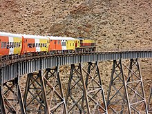 Orange, yellow and white train crossing a ravine