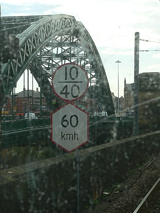 Metrication of British transport - Speed restrictions in km/h for the Tyne and Wear Metro (hexagonal sign) below mainline speed restriction signs in mph (round signs)