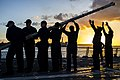U.S. Sailors aboard the guided missile destroyer USS McCampbell (DDG 85) lower the flagstaff on the flight deck as the ship departs Santa Rita, Guam, after a port visit March 28, 2014 140328-N-IP531-103.jpg