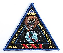 "A triangular fabric patch labeled ""XXI"""