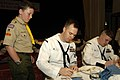 US Navy 030601-N-4055P-003 Operations Specialist 1st Class Jack Roper signs an autograph for a young American living abroad with his parents, during a dinner at the Tokyo American Club.jpg