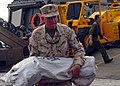 US Navy 050111-N-4383M-160 Commanding Officer, 15th Marine Expeditionary Unit (MEU), Col. Tom Greenwood, assists Sailors and Marines while unloading much needed food, water and relief supplies.jpg