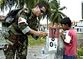 US Navy 050116-N-6817C-264 U.S. Navy Lt. Cmdr. Ramon Cestero, of San Diego, Calif., gives candy to a local Indonesian boy.jpg