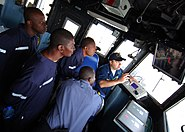 US Navy 100412-N-6138K-395 Ensign Matthew Sweet shows Tanzanian and Togolese Sailors the ship's security camera monitor aboard USS Gunston Hall (LSD 44)