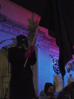 January 20, 2005 counter-inaugural protest - A masked woman holds a black flag in front of Union Station, site of the Freedom Ball.