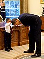 United States President Barack Obama bends down to allow the son of a White House staff member to touch his head (cropped).jpg
