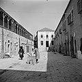 Vrouw bij een waterput in de wijk Mea Shearim het gebouw op de achtergrond is v, Bestanddeelnr 255-0402.jpg