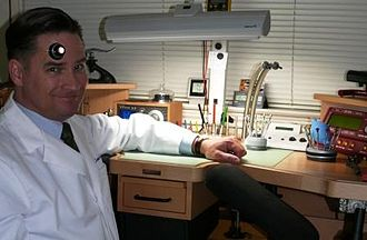 Watchmaker - A modern watchmaker at his workstation; he wears a magnifying loupe to more easily see the small parts of a watch
