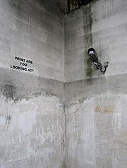 What are you looking at? — Graffiti by Banksy commenting on the neighbouring surveillance camera in a concrete subway underpass near Hyde Park in London.