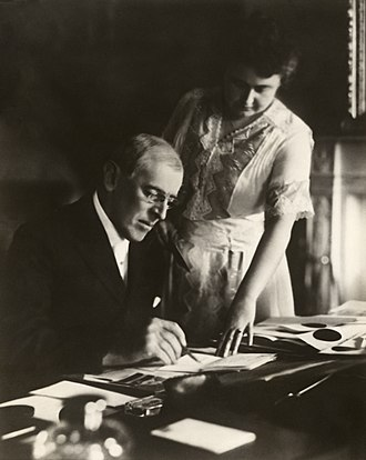 Edith Wilson - Woodrow Wilson's first posed photograph after his stroke. He was paralyzed on his left side, so Edith holds a document steady while he signs. June 1920.