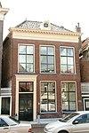 foto van Pand met omlijste deur, zesruitsvensters en hoge verdieping onder schilddak