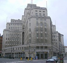 Two wings of a large white stone office building with regularly spaced rectangular windows. The building rises to twelve storeys, stepping back to a central tower surmounted by a clock and a flagpole.
