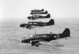 Five twin-engined military monoplanes in flight, line abreast