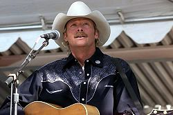 A fair-haired man wearing a white cowboy hat, singing into a microphone and playing a guitar