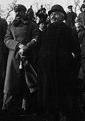 Zwart-witfoto van een man in burgerkleding, met wit haar, donkere snor, bril en donkere kleding, naast een soldaat met een dikke zwarte snor;  op de achtergrond, andere burgers en soldaten