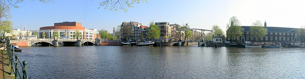View of the Stopera (left, behind the blue bridge), where the Amsterdam city hall and opera house are located, and the Hermitage Museum (right) on the Amstel