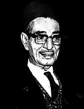 Portrait en noir et blanc d'un homme portant costume sombre, cravate noire et lunettes.