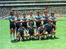 Photographie en couleurs. Les joueurs argentins, légèrement à contre-jour, posent avec sept joueurs debout et quatre devant eux, accroupis.