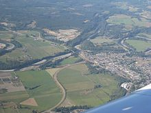 A small town surrounded by farmland and forestland, crisscrossed by rivers and roads.