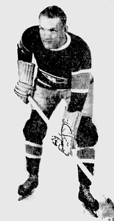 A man with short hair poses in a full ice hockey uniform, including stick and skates. He is looking slightly to his right with a serious look on his face.