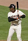 "A man in a white baseball uniform stands in the left-handed batter's box. He is holding a black bat and wearing a black batting helmet. His uniform reads ""Giants"" across the chest."