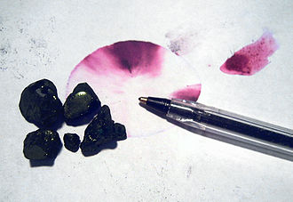 Fuchsine - Basic fuchsine pieces. The two magenta stains on the paper were made by placing one drop of ethanol-water azeotrope, centre, and water, right, on the streaks remaining on the paper after the 'crystals' were removed. The 'crystals' were then replaced and the photograph taken.