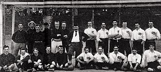 Évence Coppée Trophy - Pre-match panoramic team picture in front of a goal. At the left: team Belgium; at the right: team France; in the middle: referee John C. Keene, posing with the match ball.