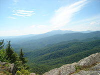 The Blue Ridge Mountains in the foreground with Grandfather Mountain in the extreme background as seen from Blowing Rock, NC.