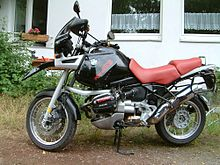 Black BMW R1100GS with red seat parked on dirt in front of a house