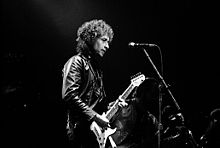 Black and white, waist high portrait of middle aged man with curly hair, leather jacket, electric guitar.