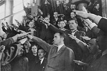 Black and white photograph of a group of men wearing business suits raising their right arms in a Nazi salute