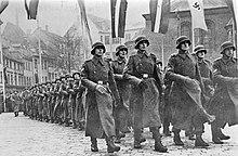uma fotografia em preto e branco de soldados em uniforme alemão e sobretudos marchando em uma coluna