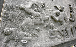 Carrickshock incident - Relief on the base of the memorial cross at the site of the incident.