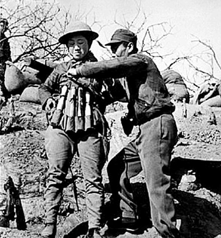 Chinese suicide bomber putting on an explosive vest made out of Model 24 hand grenades to use in an attack on Japanese tanks Chinese infantry soldier preparing a suicide vest of Model 24 hand grenades at the Battle of Taierzhuang against Japanese Tanks.jpg