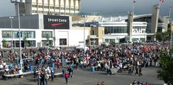 Несколько тысяч человек выстраиваются в очередь, пока волонтеры разносят еду.  На заднем плане стоит большой торговый центр.