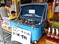 Cold Container with Golden Tea and Bottled Water on Table 20140705.jpg