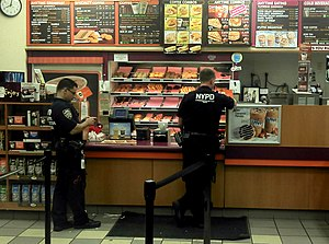 Stereotype - Police officers buying doughnuts and coffee, an example of perceived stereotypical behavior in North America.