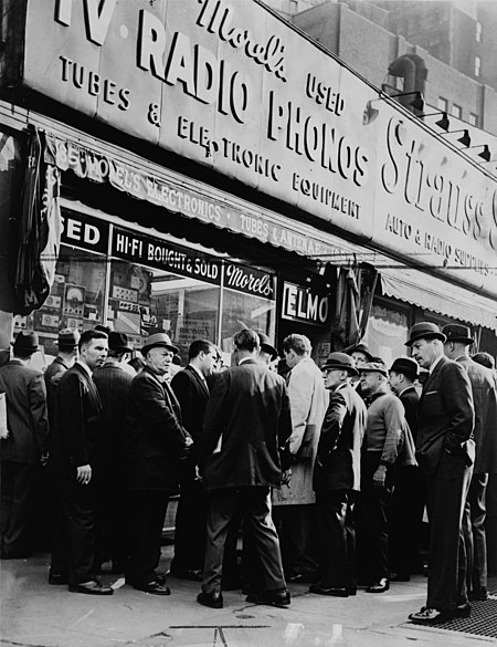 A crowd gathers near an electronics shop at Greenwich and Dey streets after John F. Kennedy's assassination in 1963. Crowds listening for news on Kennedy NYWTS.jpg