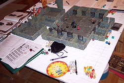 An elaborate example of a D&D game in progress. Among the gaming aids shown are dice, a variety of miniatures and some miniature scenery.